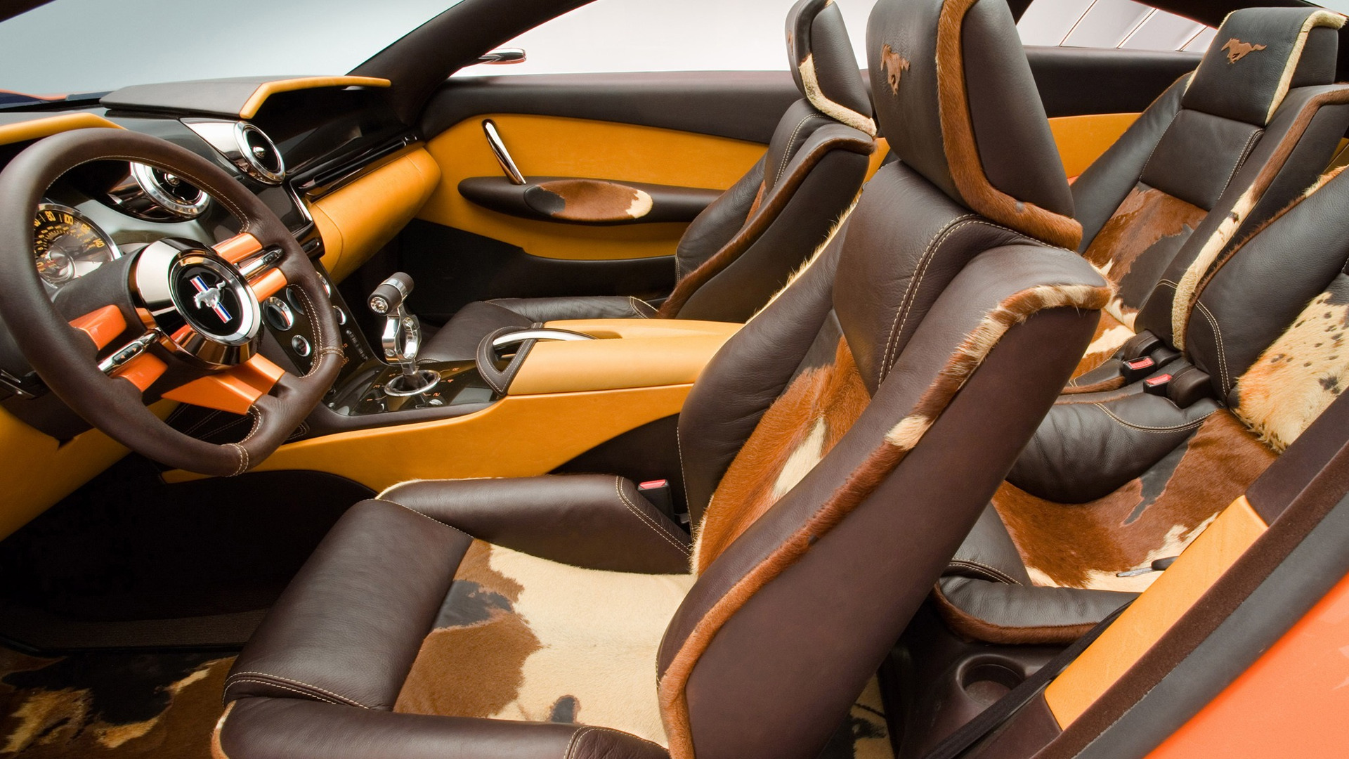 Ford Mustang Giugiaro concept: The interior of the Mustang Giugiaro concept features a dramatic instrument panel that sweeps the width of the car; circular gauges that project from behind the steering wheel; dark brown horsehide-covered headrests with horse logo accents; and seat cushions and backrests elaborately upholstered in dark brown mottled horse hides.