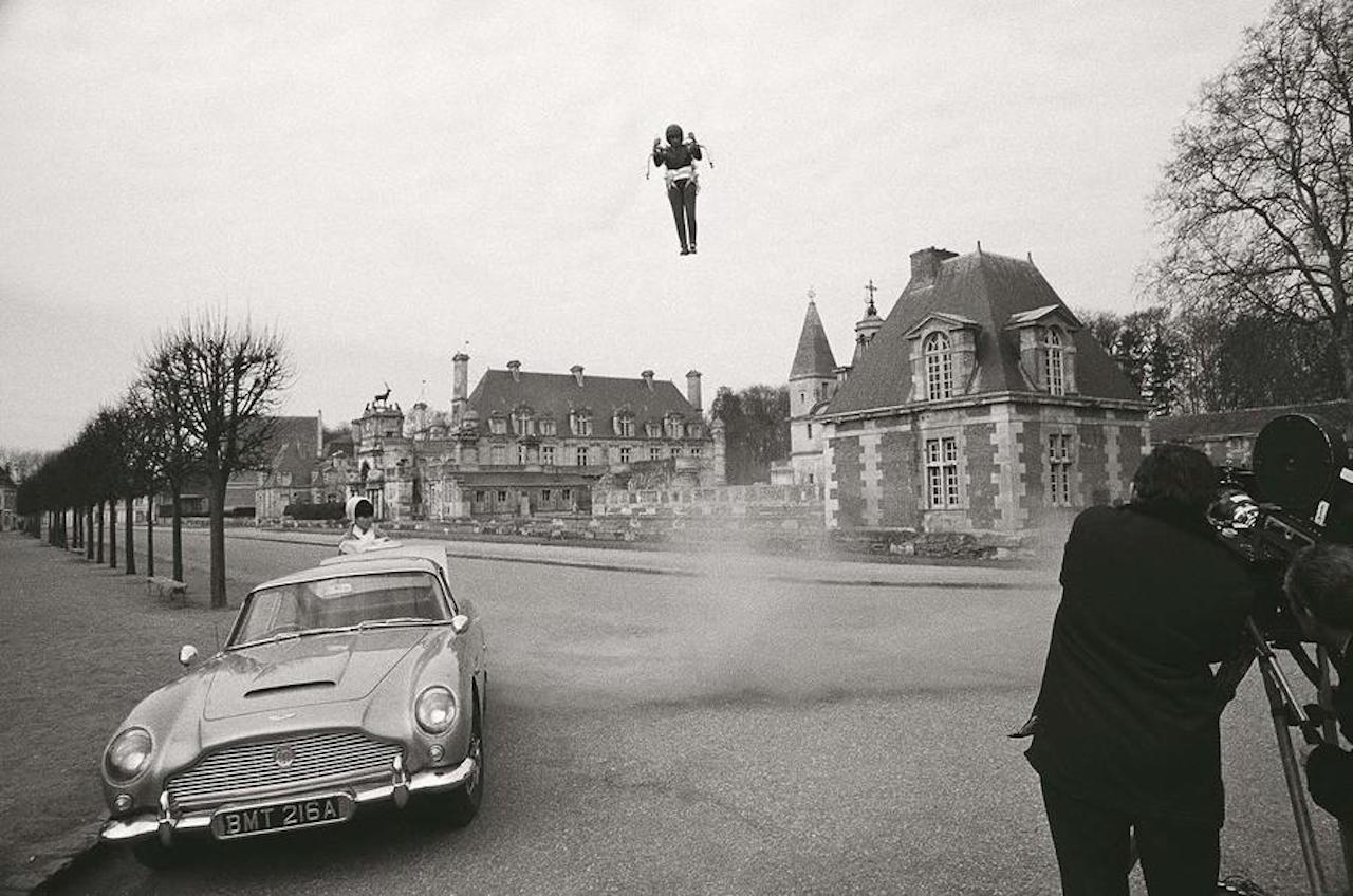 The force of the jet pack can be seen whipping up the dust and stones on the road as it comes into land.Waiting at the Aston Martin DB5 is French spy Madame LaPorte. played by MARYSE GUY MITSOUKO.
